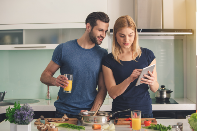 A man and a woman standing in a kitchen preparing food