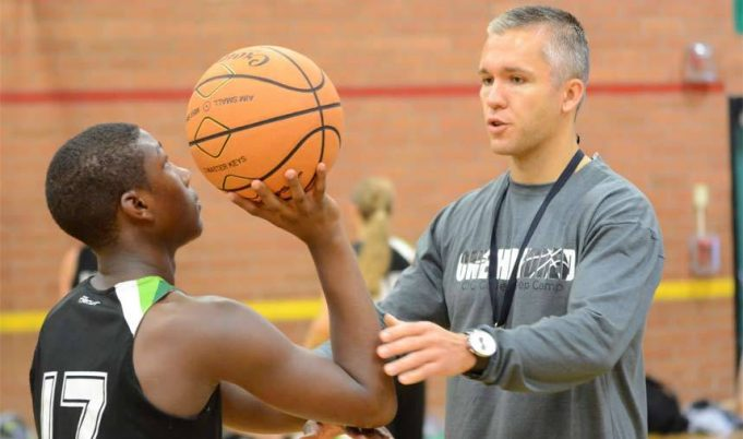 A boy Playing basketball with coach